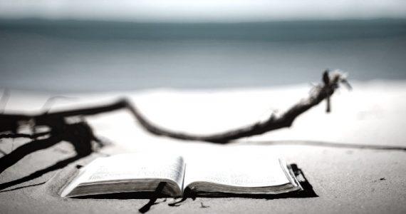 open bible resting on a sandy beach
