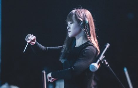 young woman conducts the orchestra